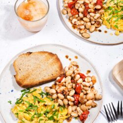 The breakfast is served with whole grain toasts on two plates that are on the white table with two forks and a cup of coffee with milk | Hurry The Food Up