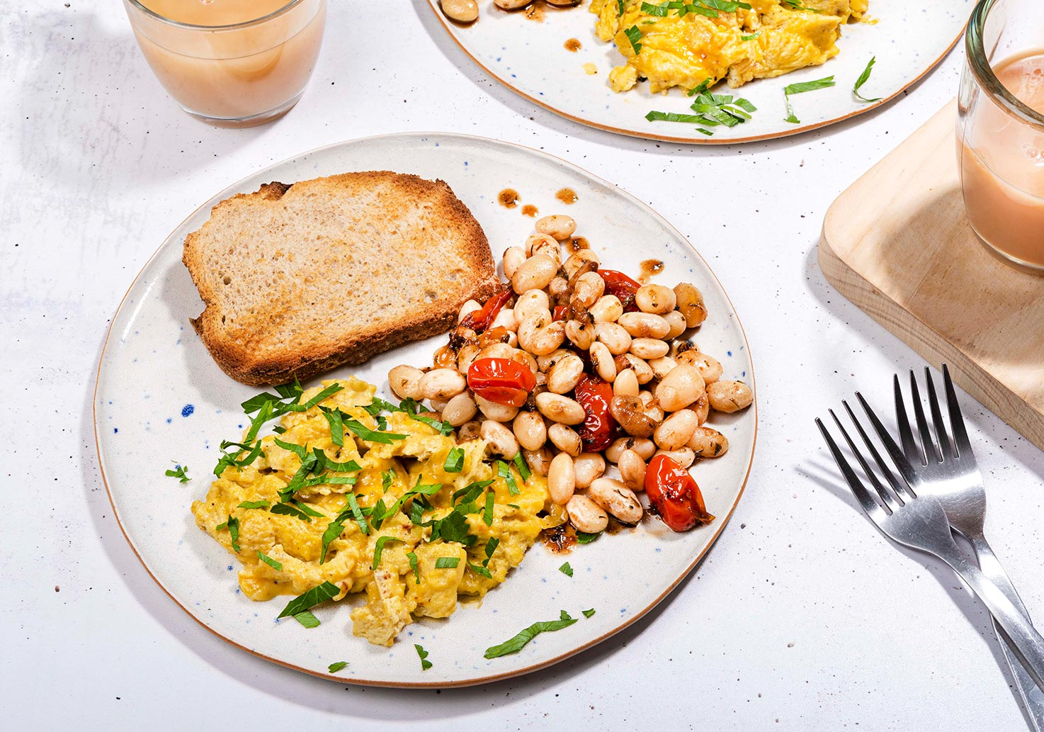 The breakfast is served with whole grain toast on a plate that is on the white table with two forks and a cup of coffee with milk and tea | Hurry The Food Up