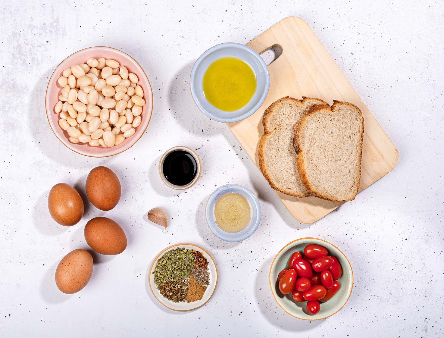The breakfast ingredients like white beans, eggs, cherry tomatoes, bread slices, olive oil, garlic etc. | Hurry The Food Up