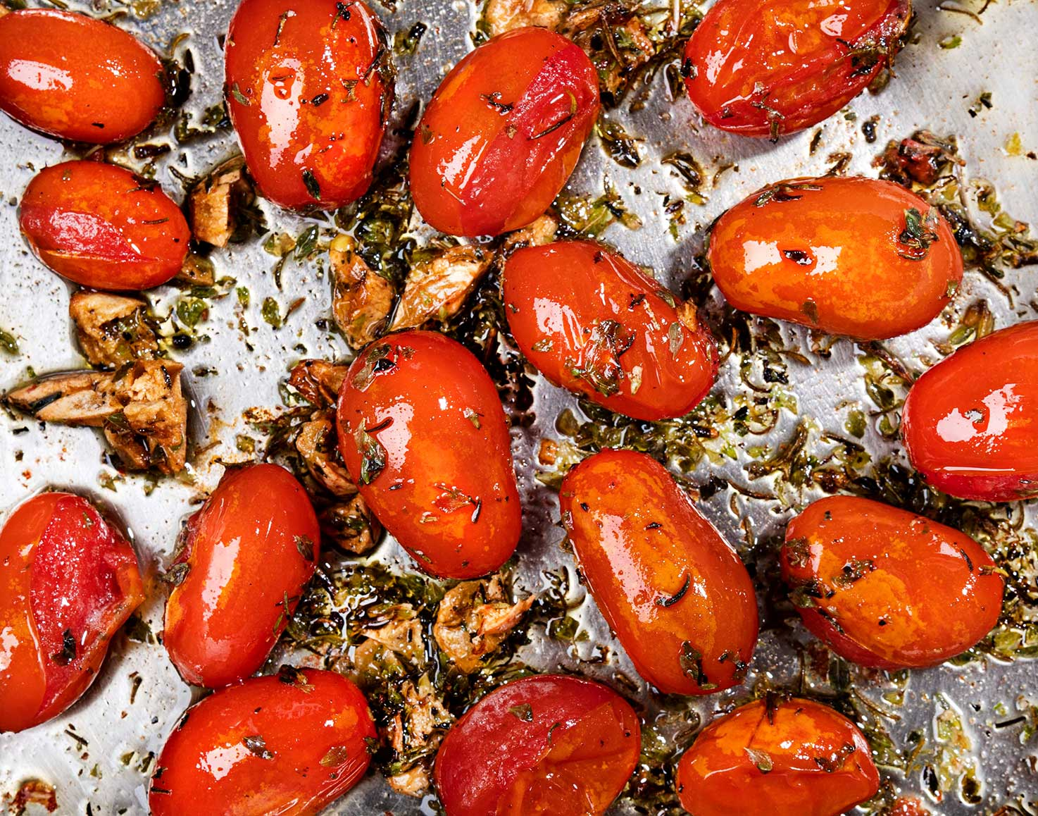 Cherry tomatoes are cooking in the pot with olive oil, smashed garlic clove and spices | Hurry The Food Up
