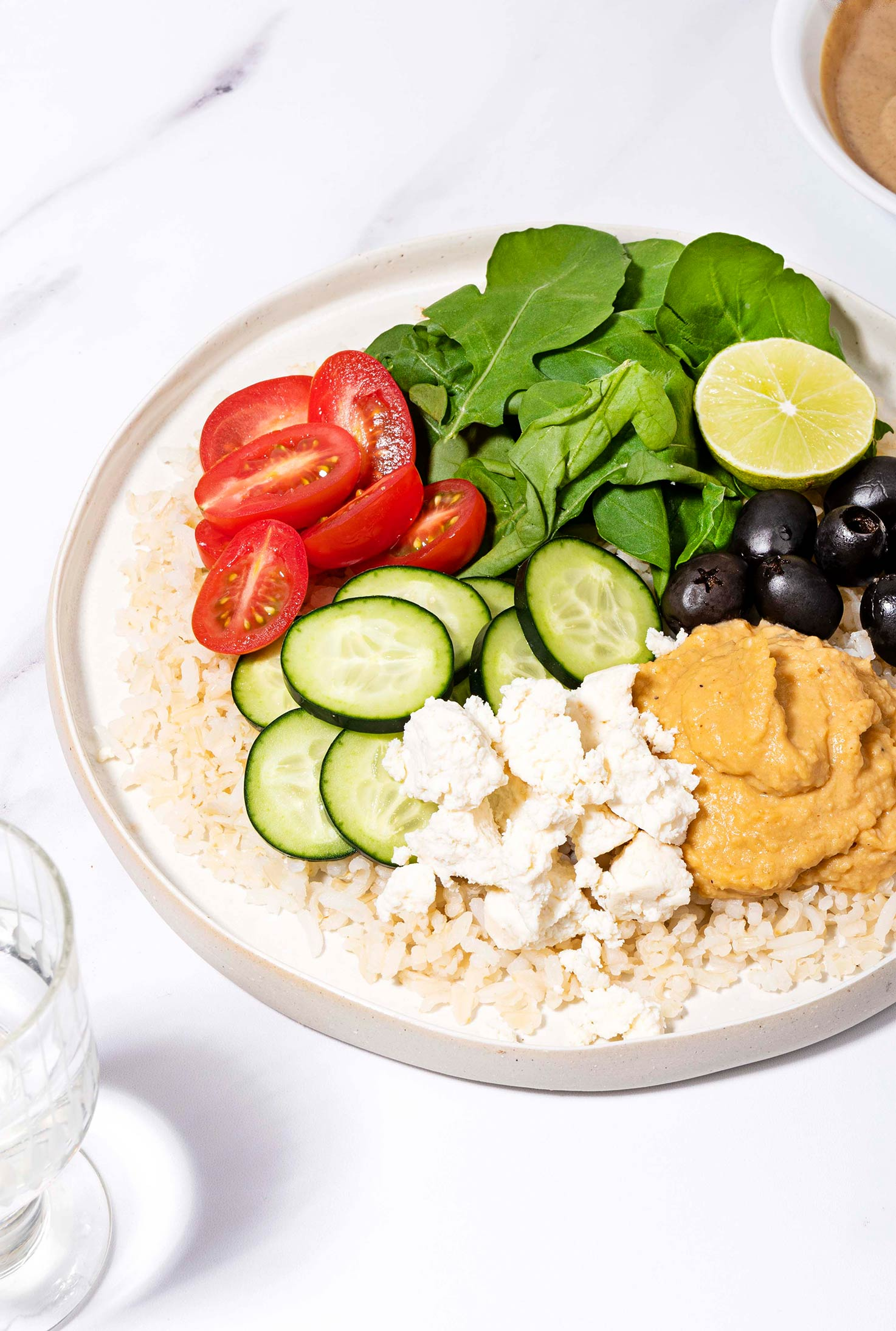 Mediterranean Rice Bowl is served on the plate with a glass of water and tahini sauce in the bowl   Hurry The Food Up