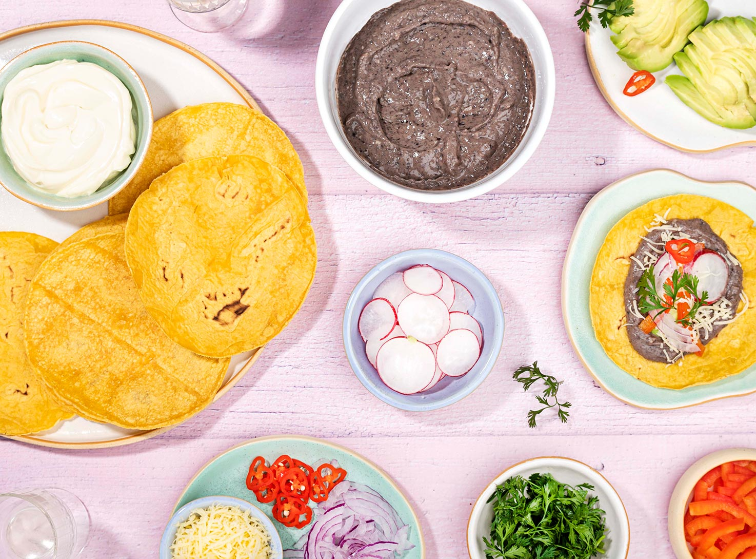 The tortilla is topped with refried beans radish slice, chopped onion, cilantro and grated cheddar cheese that is on the table with all the prepared ingredients | Hurry The Food Up