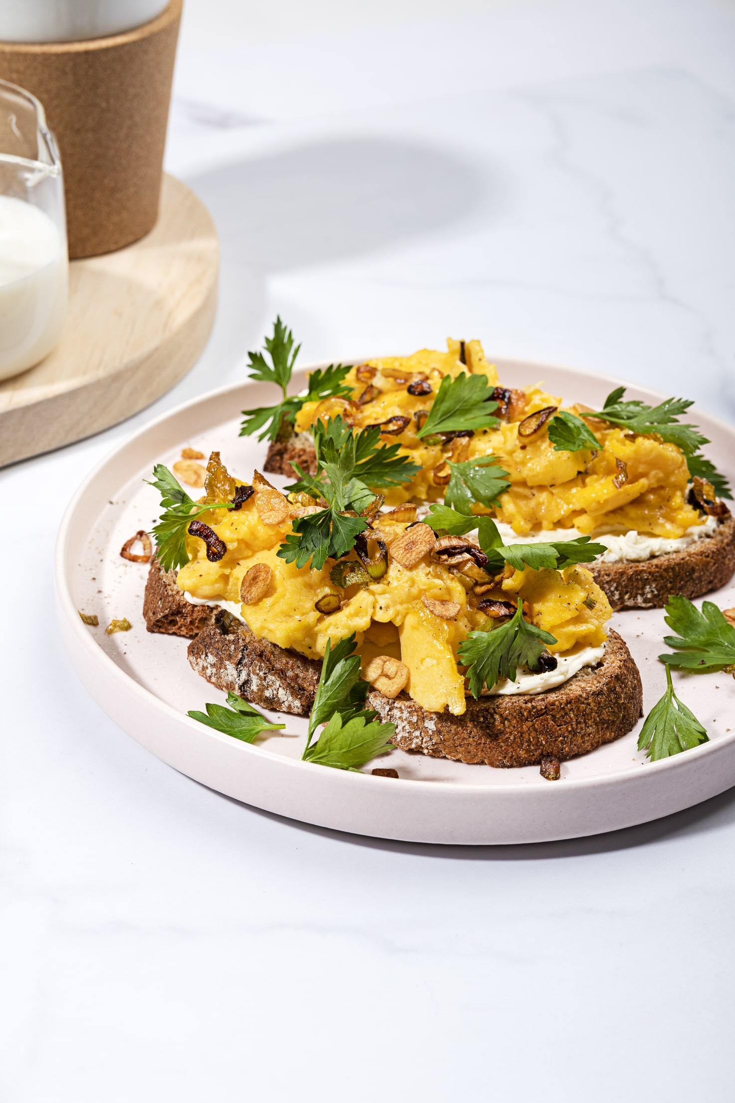 A plate of scrambled eggs taken from a side-long angle, with a milk jug and the bottom of a coffee mug visible in the lefthand corner | Hurry The Food Up
