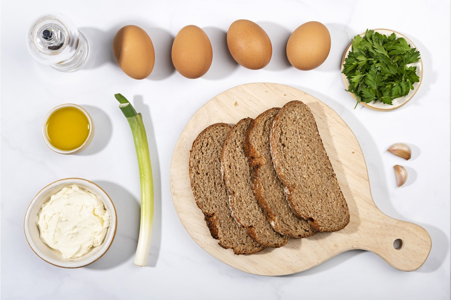 The ingredients for scrambled eggs including 4 slices of brown bread on a wooden board, a spring onion, a bowl of cream cheese, a small bowl of olive oil, a pepper grinder, 4 eggs, a plate of parsley and two garlic cloves | Hurry The Food Up