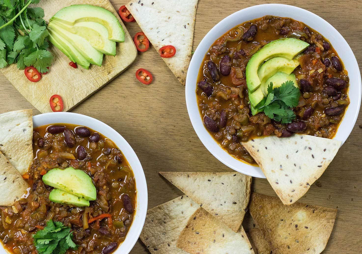 Meatless chili con carne is served in two bowls with tortillas, and slices of avocado | Hurry The Food Up