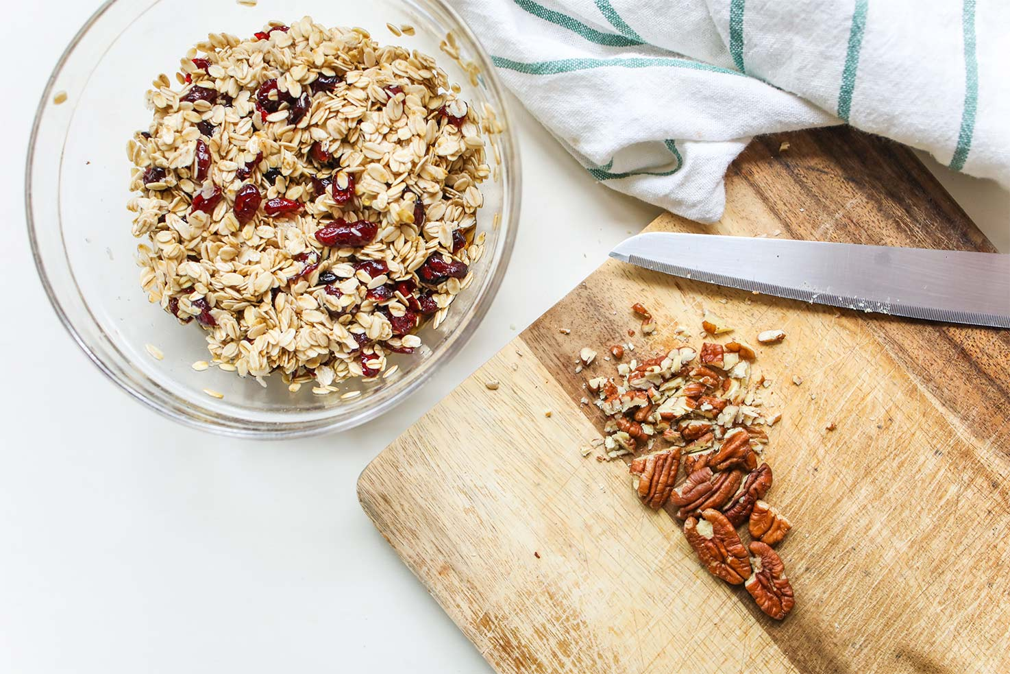 Oats with raisins in the bowl with chopped pecans on the chopping board with knife | Hurry The Food Up