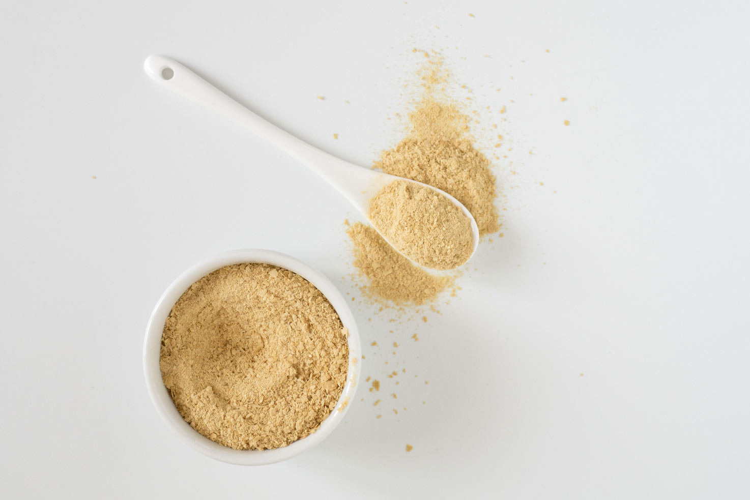 Nutritional yeast in the small bowl with white spoon | Hurry The Food Up