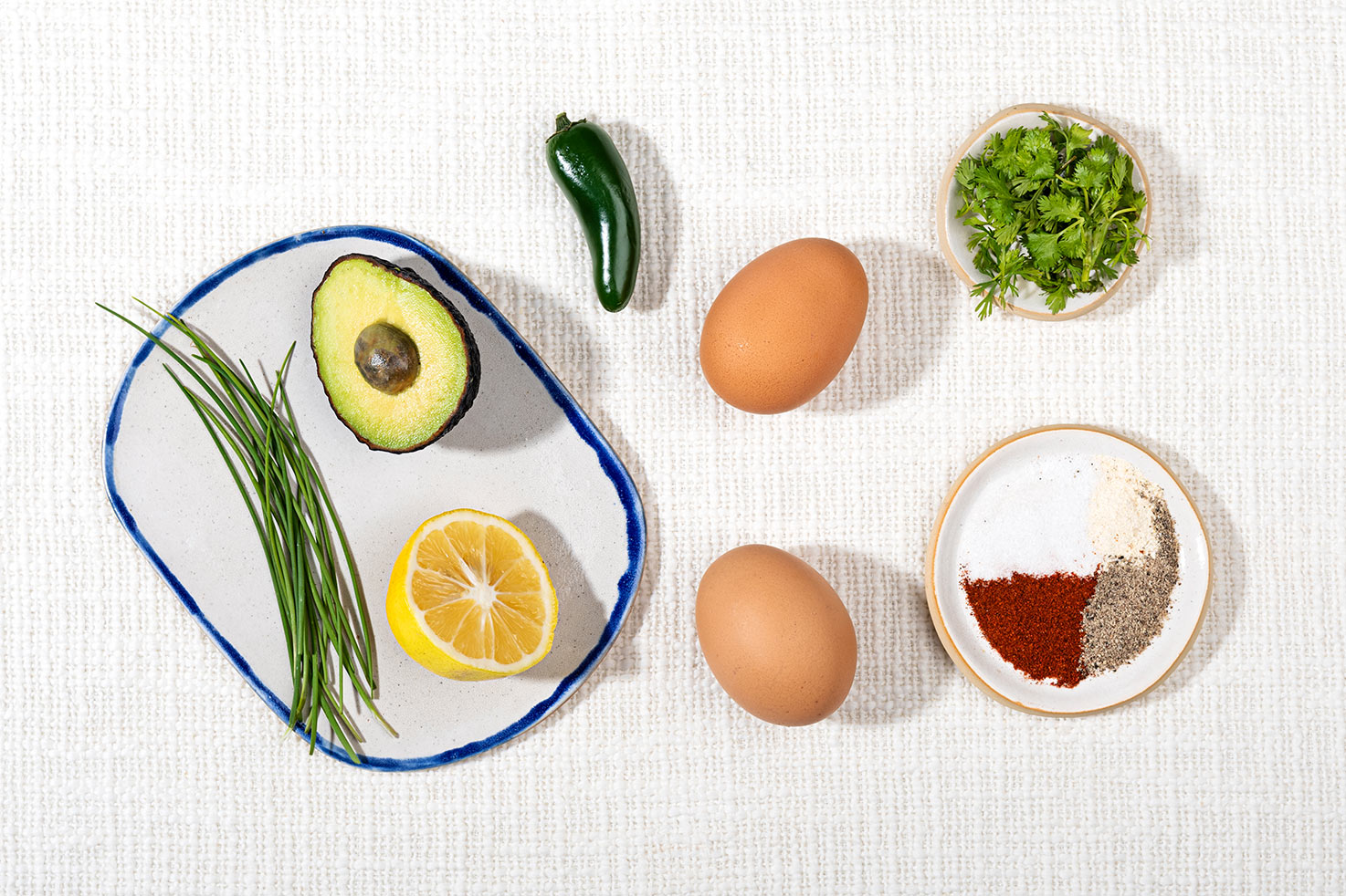 The recipe ingredients like eggs, avocado, lemon, slices, jalapeño, cilantro etc. | Hurry The Food Up