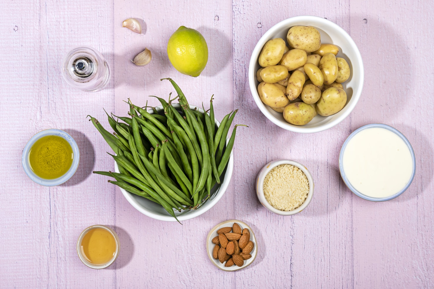 The ingredients for a green bean casserole are laid out on purple painted planks. These include green beans, potatoes, a lime, 2 garlic cloves, pepper, olive oil, panko breadcrumbs, honey, low-fat sour cream and honey. | Hurry The Food Up