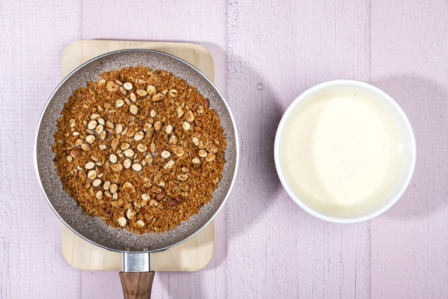 The crispy topping of breadcrumbs, garlic and almonds is in a pan on a wooden board, and the low-fat sour cream is in a bowl next to it. | Hurry The Food Up